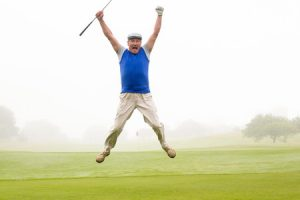 38146792 - excited golfer jumping up and smiling at camera on a foggy day at the golf course