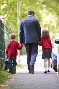 30999994 - father walking to school with children on way to work