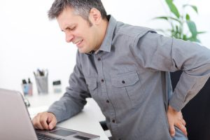 43001190 - image of a young man having a back pain while sitting at the working desk