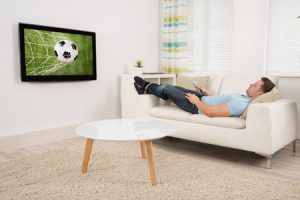 51450368 - relaxed mid adult man lying on sofa while watching football match on television at home